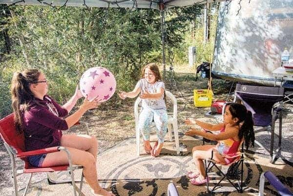 Cheyanne Jones, 15, left, Madison Flanagan, 7, and Ava Catholique-Herback, 4, toss a ball around at a Fred Henne Territorial Park campsite last August. - Robin Grant/NNSL photo