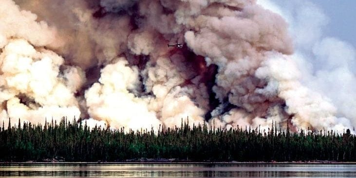 A helicopter works on a forest fire near Gameti last year as part of a burnout operation that aimed to keep the fire from creeping closer to a lake near the community. NNSL file photo.