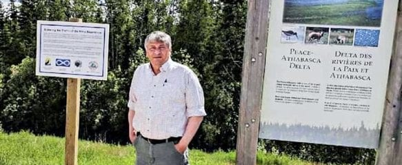 Ken Hudson, president of Fort Smith Metis Council, stands by signs Metis leaders posted in Wood Buffalo National Park in 2017 that illustrate the history of the Metis experience since the park was formed in 1921. Photo courtesy of Northwest Territory Metis Nation.