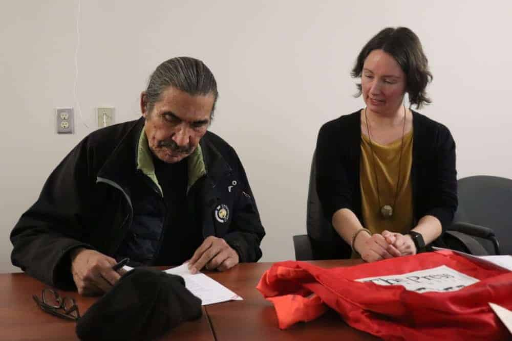 JC Catholique, left and Erin Suliak sign the donation agreement that allows 200,000 Native press photos to be digitally archived. Dylan Short/NNSL photo
