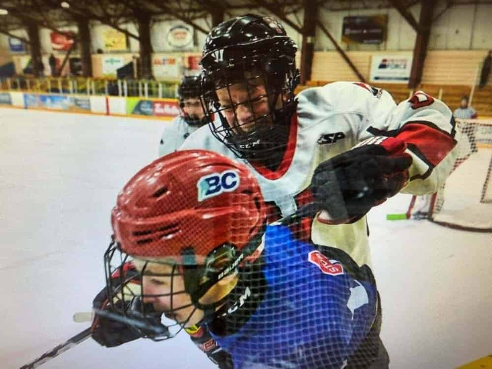 Matthew Gillard checks a North Central Cougars player into the boards during the Yukon Rivermen's weekend series in the BC Hockey Bantam Tier 1 Zone League in Whitehorse in November 2018. Gillard is now a member of the Victoria Royals after being selected by the team in the seventh round of the Western Hockey League bantam draft on Wednesday. photo courtesy of April Desjarlais