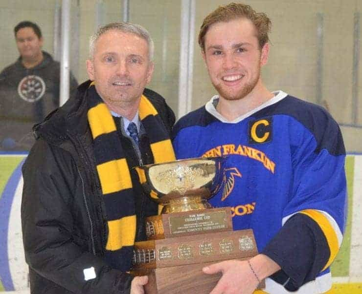 Dean MacInnis, principal of Sir John Franklin High School, presents Jack Panayi, captain of Sir John Franklin's boys team, with the championship trophy after the Falcons beat St. Pat's in the Wade Hamer Challenge Cup boys game in November 2017. NNSL file photo