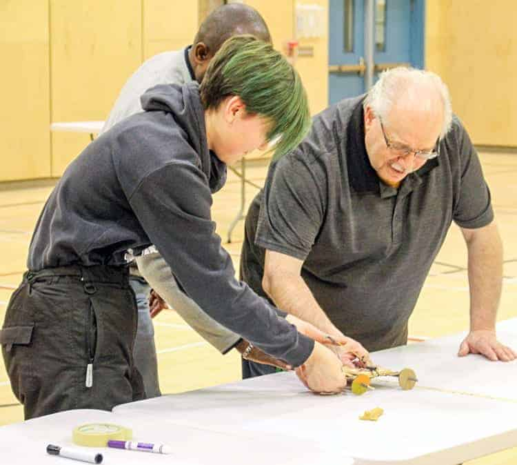 Student Kendra Kringayark tests out her project while teacher Gregg Durrant, back, and principal Aubrey Bolt measure the distance reached during the Acura STEM Challenge at Tuugaalik High School in Naujaat on Nov. 16, 2018. Photo courtesy Julia MacPherson