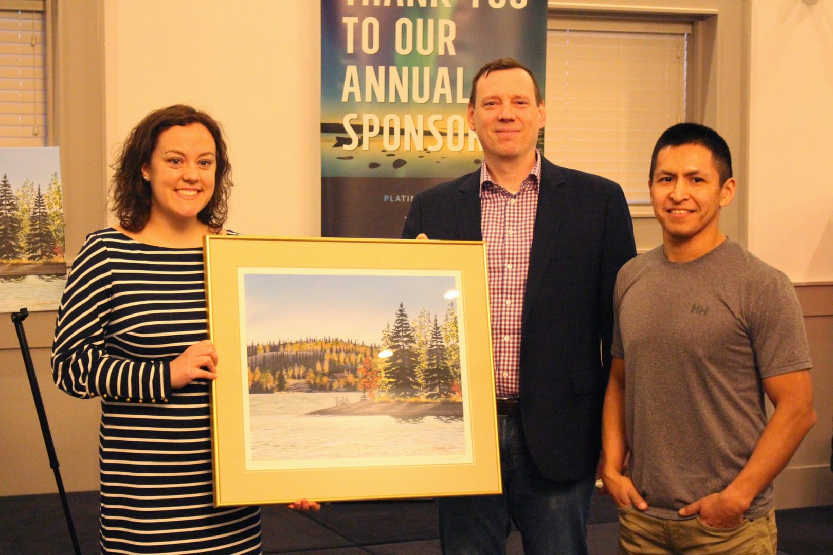 Brett McGarry/ NNSL Photo NorthwesTel's Paul Gillard and Darrell Chocolate, right, give a print of Chocolate's 'Serene Fall Season' to Mayor Rebecca Alty, to be hung in city hall. A print was also given toJohn MacDonald, Assistant Deputy Minister of Education, Culture and Employment.