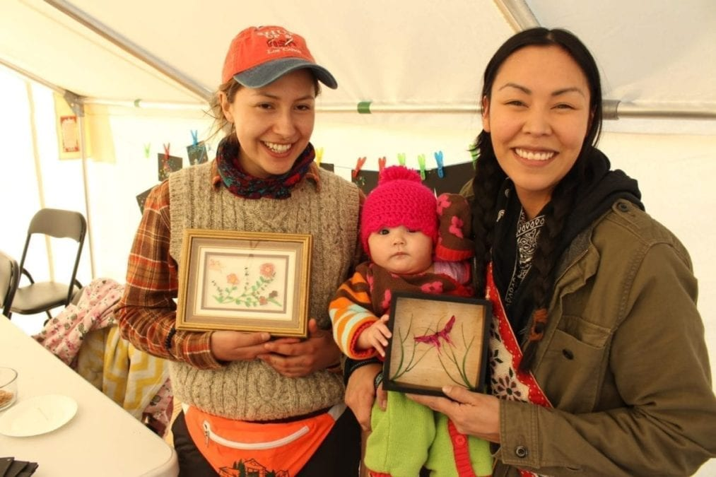 Jiah Dzentu, left, with Charlotte Overvold, right, and her child Oceane Snow Overvold-Ryan with some pieces of art created with the bones and scales of fish, materials often discarded. Brett McGarry/NNSL Photo