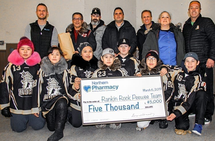 Rankin Rock peewee players, front row from left, Erin Kubluitok, Kaylen-Janne Nakoolak, Sophia Kaludjak, Kylan Saviakjuk, Jaidyn Verbeek, Kadin Eetuk and Simon Wiseman proudly display the $5,000 donation the team received from the Northern Pharmacy. Also taking part in the presentation are, back from left, Tim Smith (Northern Pharmacy), Hunter Totoo (donated 2,000 GN pins to the team), Joe Verbeek (Rankin Rock coach), Larry Fortes (Northern store), Dave Chatyrbok (Northern store), Rae-Lynn Steadwell (Northern store) and Dave Wiseman (Rankin Rock coach) in Rankin Inlet on March 7, 2019. Darrell Greer/NNSL photo