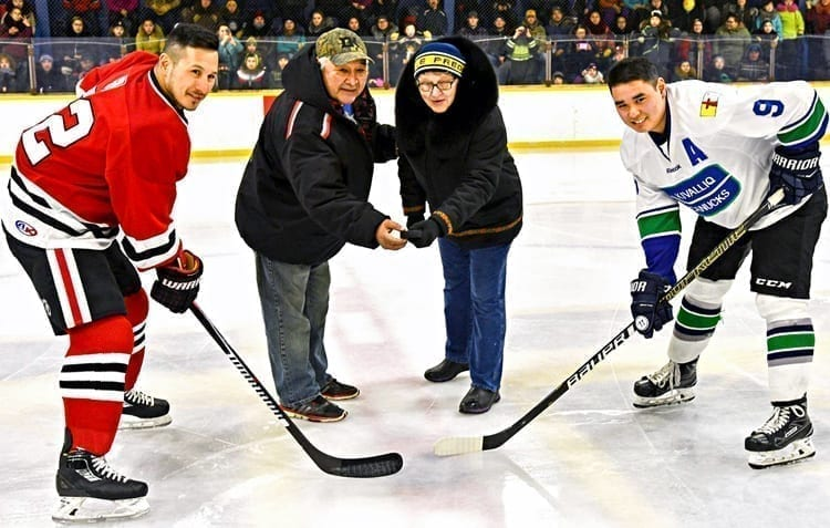 Rose and Barney Tootoo conduct the ceremonial faceoff with Jordin Tootoo, left, and Piqut Nukapiak to launch the 2019 Terence Tootoo Memorial senior men's championship in Rankin Inlet on March 8, 2019. NNSL file photo