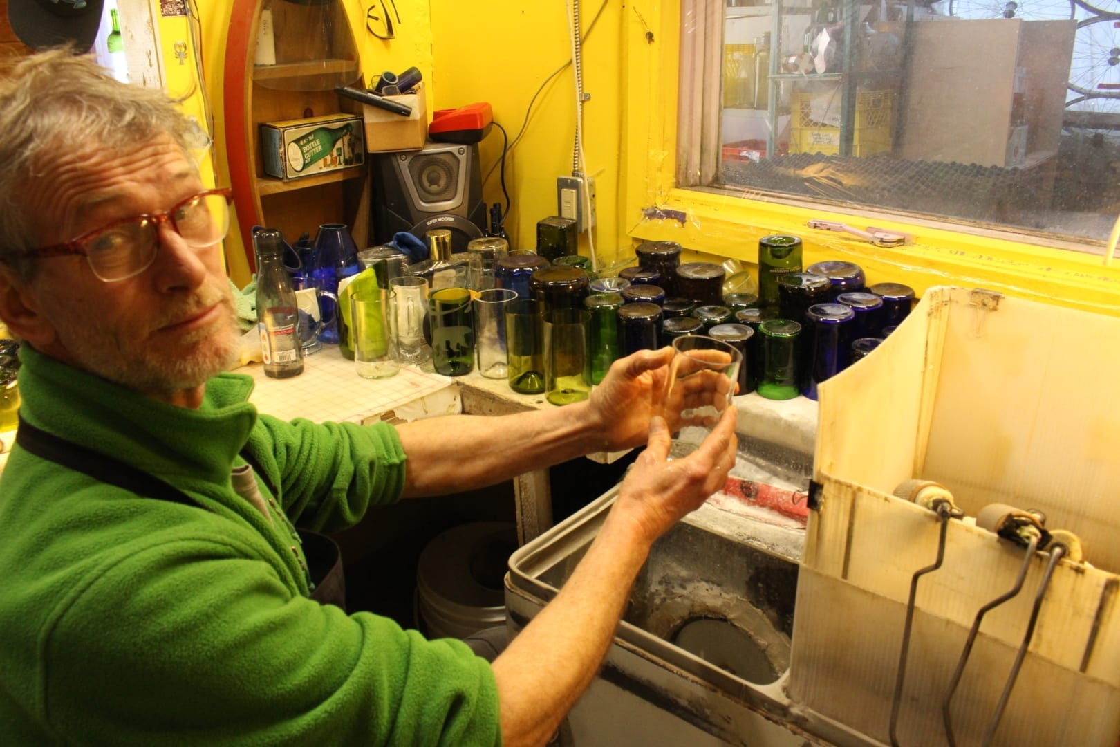 Matthew Grogono shows off a freshly cut glass that will be ground down and polished on his one of a kind custom 1955 Hoover washing machine he built with Gary Vaillancourt. He's been using the machine since he started Old Town Glassworks in 1994. Brett McGarry/NNSL Photo