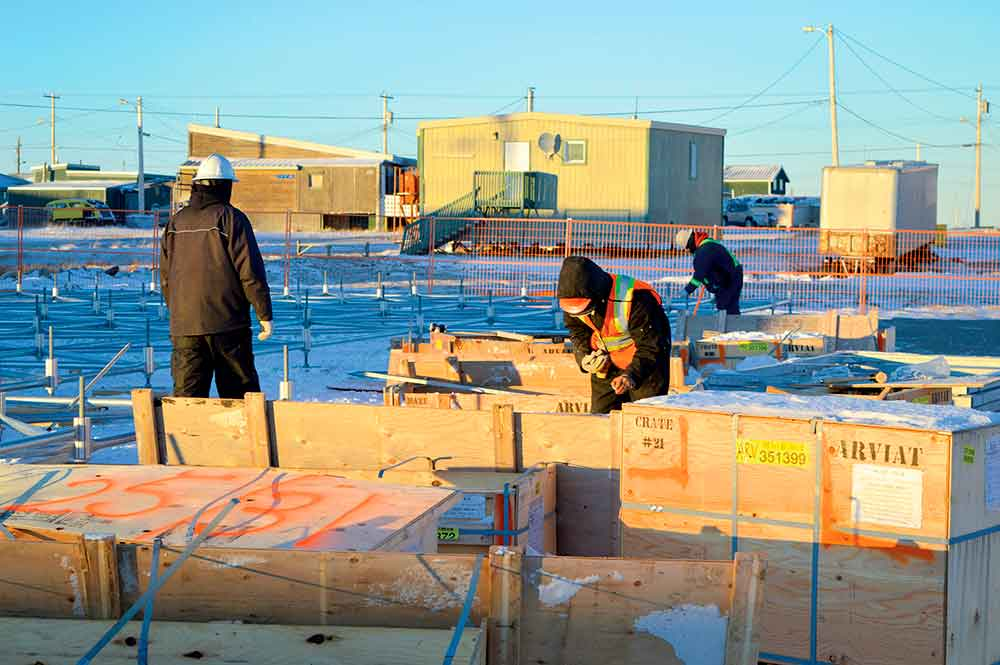 Construction workers open crates of supplies to build new homes in Arviat in October. Twenty units are scheduled to go up during the 2019-2020 construction season. photo courtesy of Nunavut Housing Corporation