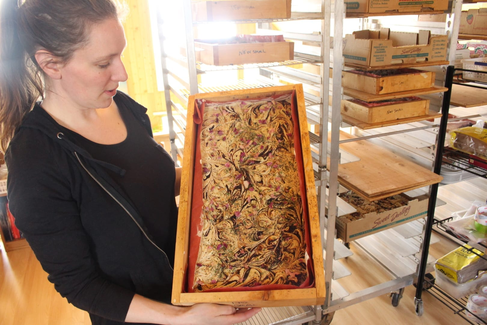 Amy Maund showing a tray of natural soaps infused with harvested vegetation from the NWT. Maund makes a half dozen different kinds of natural soaps, which are a small portion of Laughing Lichen's complete product line. Brett McGarry NNSL/Photo