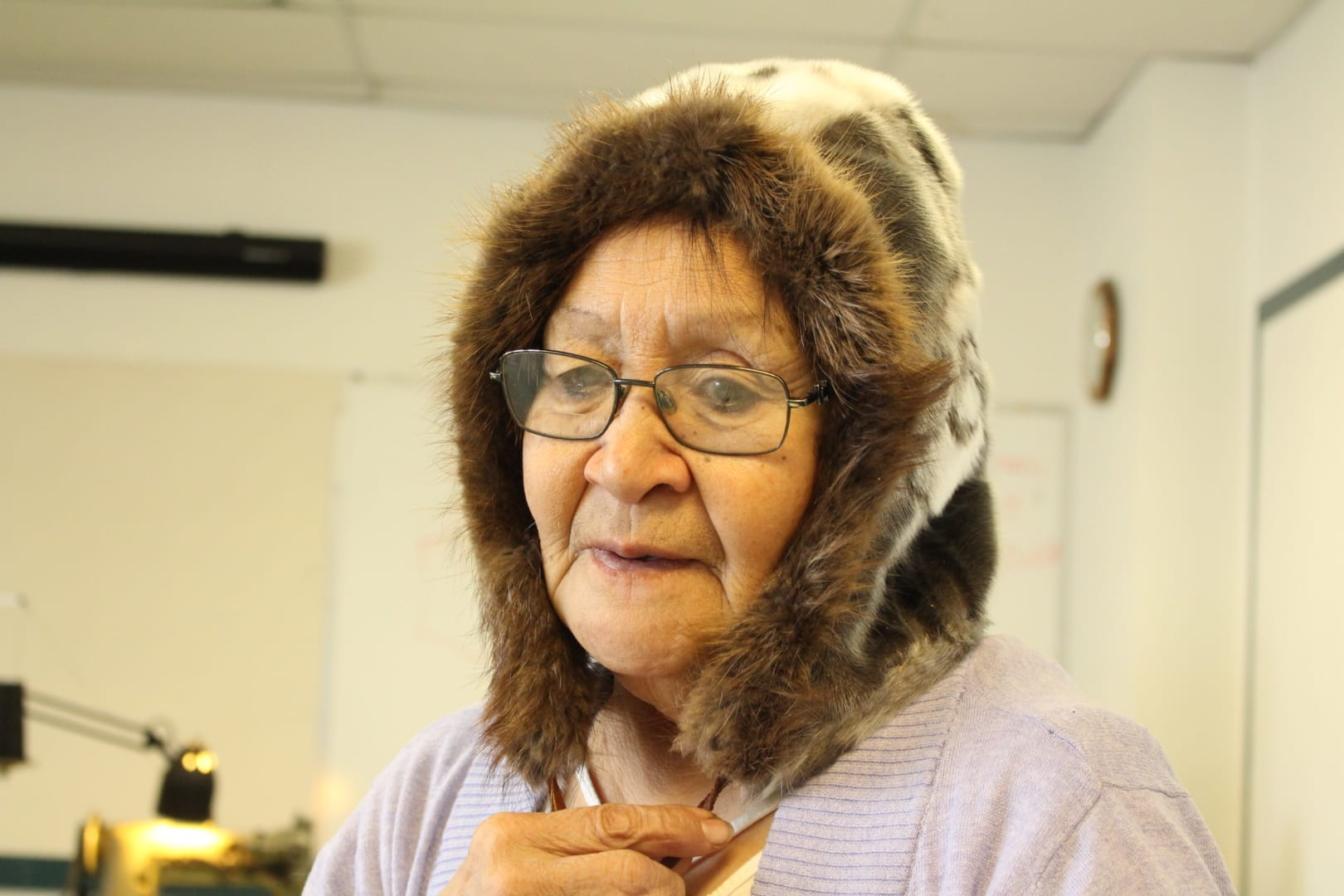 "Susie Nakashuk-Zettler ""showing off her good side"" while sewing a piece of seal skin. She said being involved in the workshop and being surrounded by wonderful Indigenous artisans brought tears to her eyes. Brett McGarry"