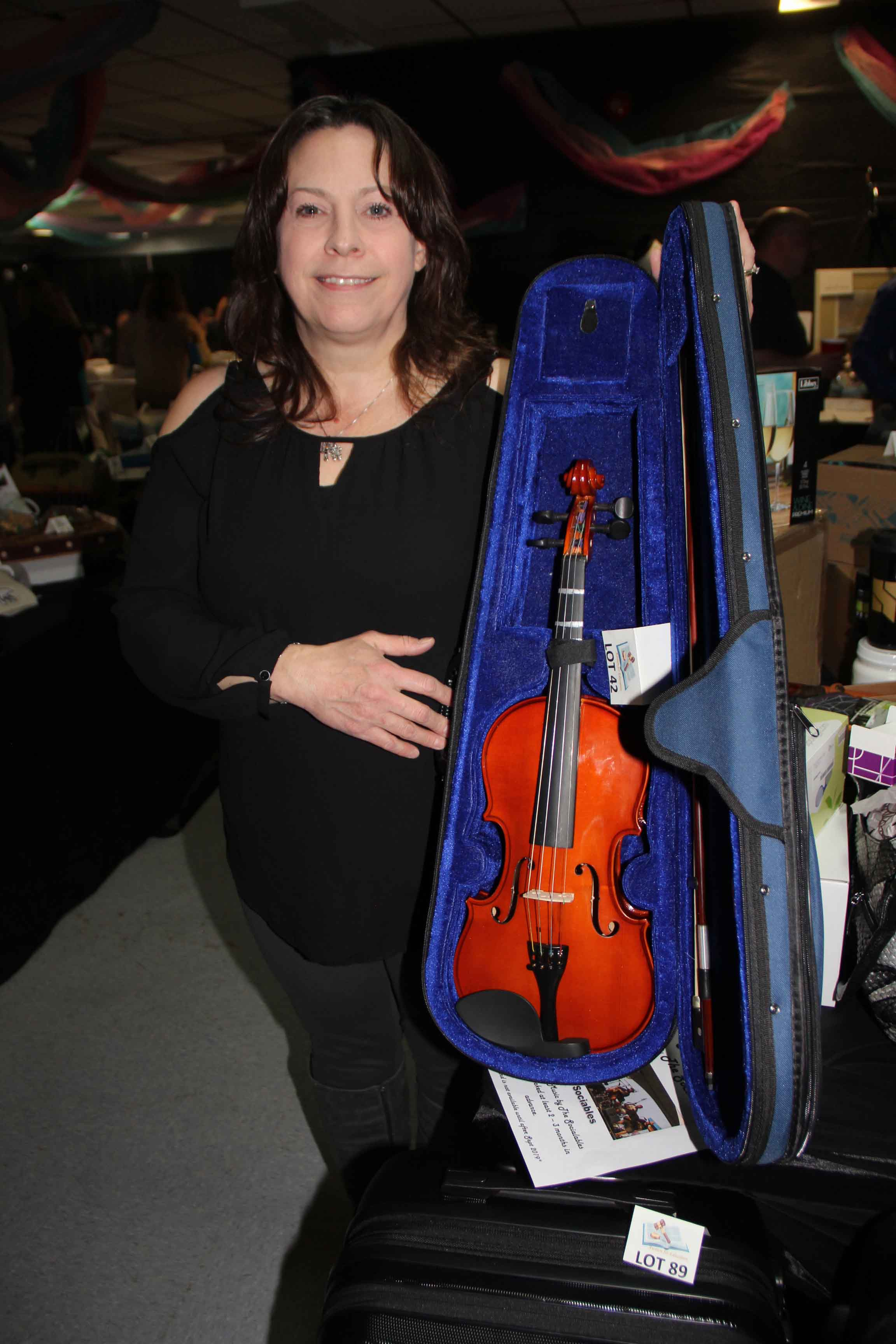 Jill Morse, an organizer of the new Auction for Education, displays a fiddle – one of the many items up for bids at the May 4 fundraising event. It was presented by the Parent Action Committees at the four schools in Hay River to replace the former Hay River Playschool Auction. Paul Bickford/NNSL photo