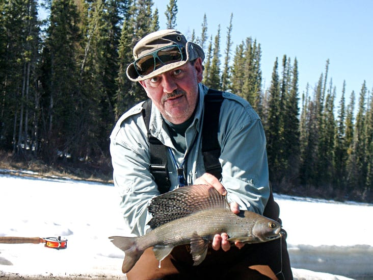 A rare photo of Mac Stark without sunglasses and holding an Arctic grayling from the Kakisa River in 2005, obviously a spawning male judging by the milt dripping from its anal fin. Mac died on Oct. 6 last year. A bench dedication ceremony will be held for him at the Kakisa River day use area on June 9. photo courtesy of John Nishi