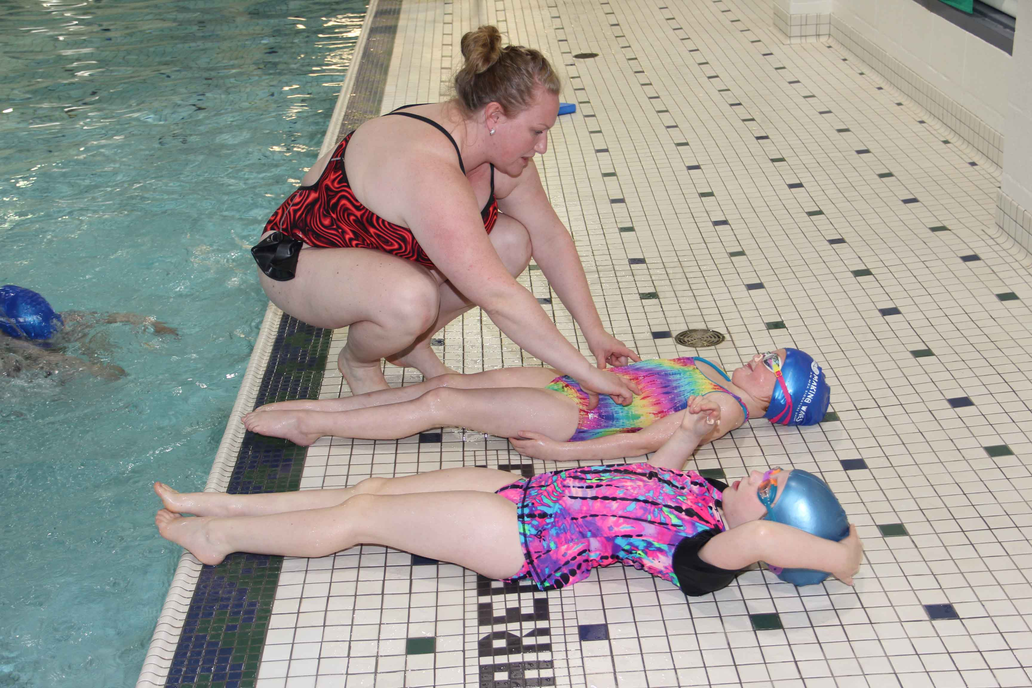 Amy Gagnon, the coach of the new synchronized swimming club at the Hay River Aquatic Centre, shows her daughter Sophie Gagnon how to tighten her stomach muscles, a technique to help a swimmer remain flat on the surface of the water. Sophia Touesnard is also in the eight-member club. Paul Bickford/NNSL photo