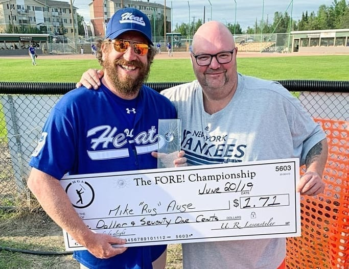 Mike Auge, left, receives his winner's cheque of $1.71 for winning the FORE! Championship from Shaun Morris, president of the Mediocre Golf Association's Yellowknife chapter, at Tommy Forrest Ball Park on June 21. photo courtesy of Shaun Morris