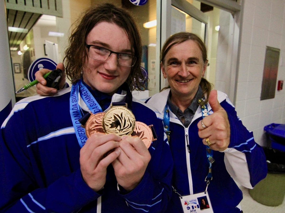 Leo Konge, left, shows off his hardware - one gold and two bronze - that hes won at the Western Canada Summer Games in Swift Current, Sask., as coach Jane Mooney gives the thumbs-up. He won gold in the 50-metre butterfly on Sunday.