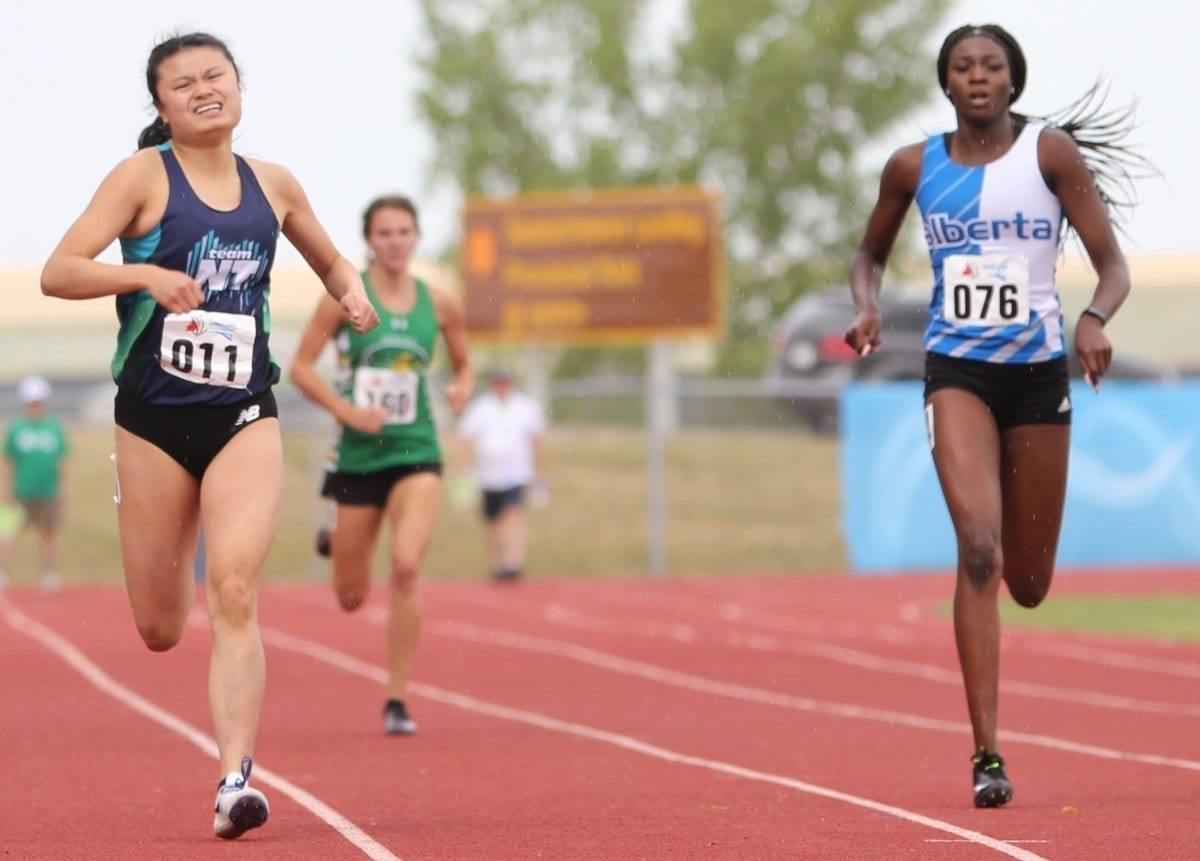 Fiona Huang of Hay River, left, is neck-and-neck with Anok Tiordit of Alberta down the stretch in the heats of the girls 400-metre dash at the Western Canada Summer Games in Swift Current, Sask., on Thursday. photo courtesy of Rob Hart