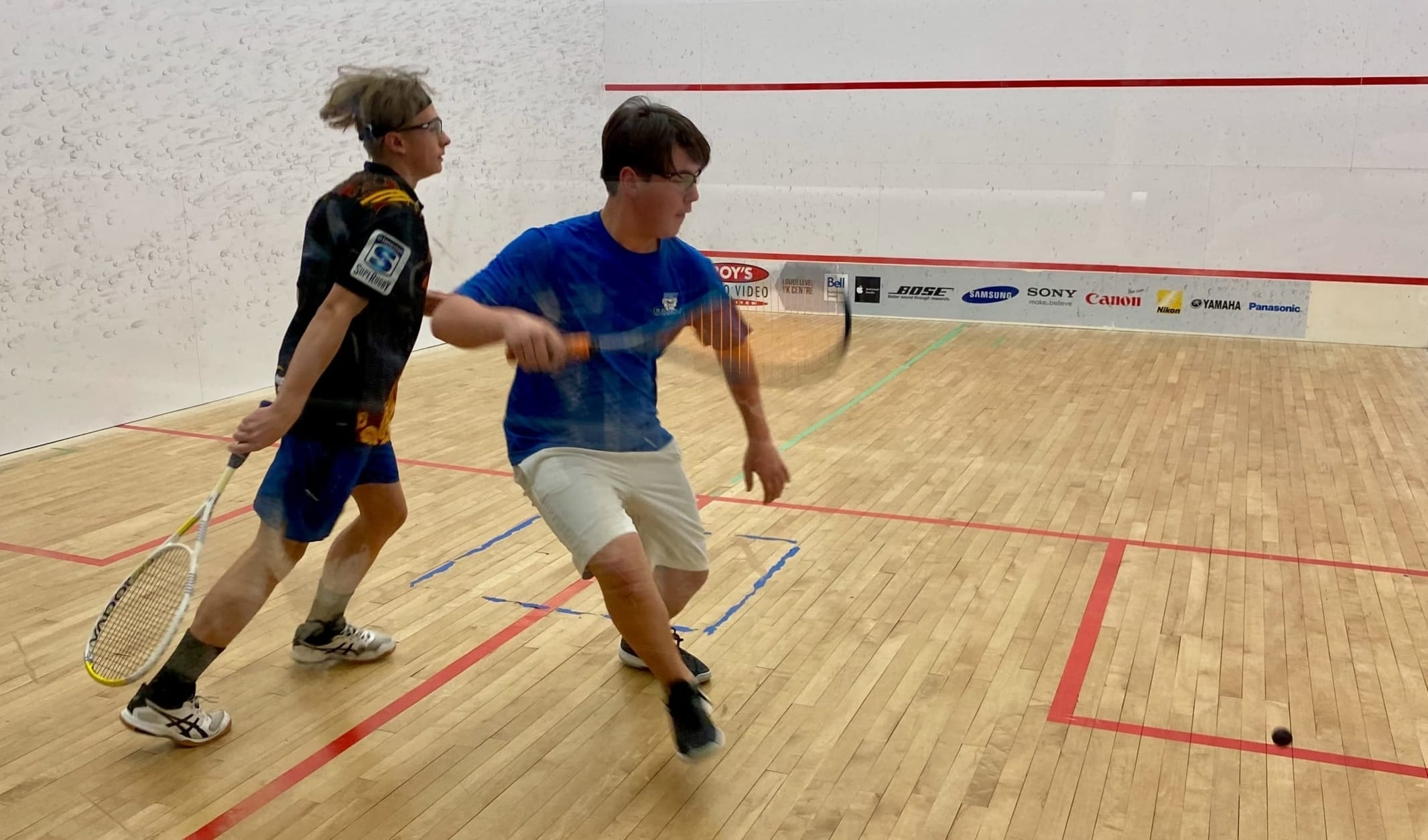Carter Robertson, right, gets set to return a shot as Loic Hipfner tries to avoid getting in his way during the A division final of the NWT Junior Squash Championships at the Racquet Club on Sunday. photo courtesy of Jeff Hipfner