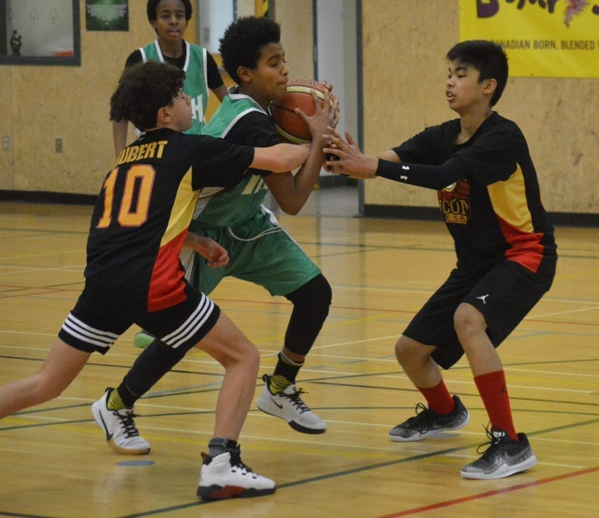 Francesco Stefanos of St. Pat's drives the lane against two defenders from Hay River's Ecole Boreale during Grade 8 boys playoff action in the Junior Cager basketball tournament at St. Pat's Gymnasium on Sunday. James McCarthy/NNSL photo