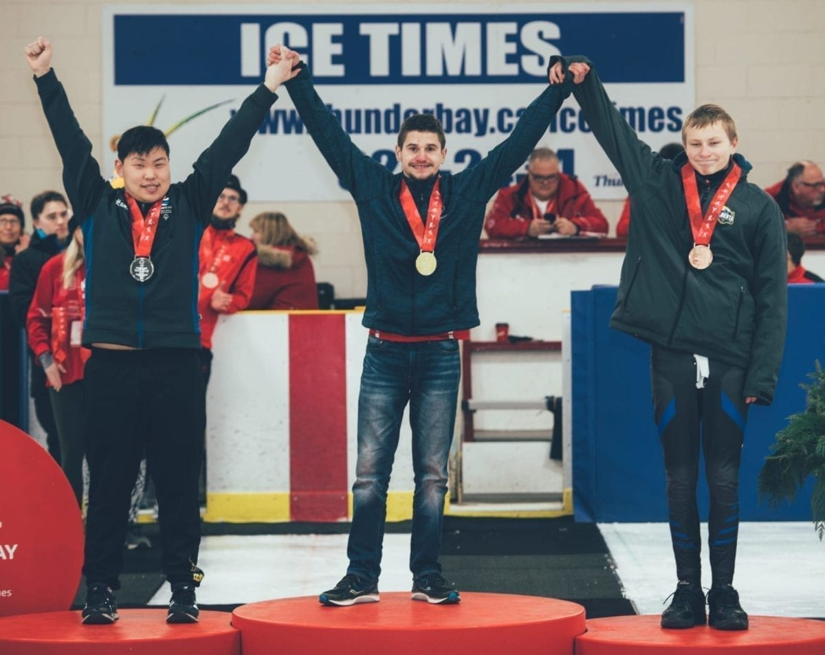 Josh Boudreau, centre, raises his arms in victory after winning gold in the men's 16-21 division in speedskating at the Special Olympics Canada Winter Games in Thunder Bay, Ont., on Feb. 28. With him are silver medallist Nicholas Chow of B.C., left, and bronze medallist Tyler Larson of Alberta. photo courtesy of Special Olympics Canada