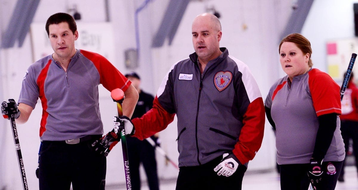 Robert Borden, left, Jamie Koe and Kerry Galusha plan their next shot during action at the 2015 Canadian Mixed Curling Championship in North Bay, Ont. Koe and his rink earned a silver medal that year after dropping the final to Saskatchewan. Brian Doherty/Curling Canada photo