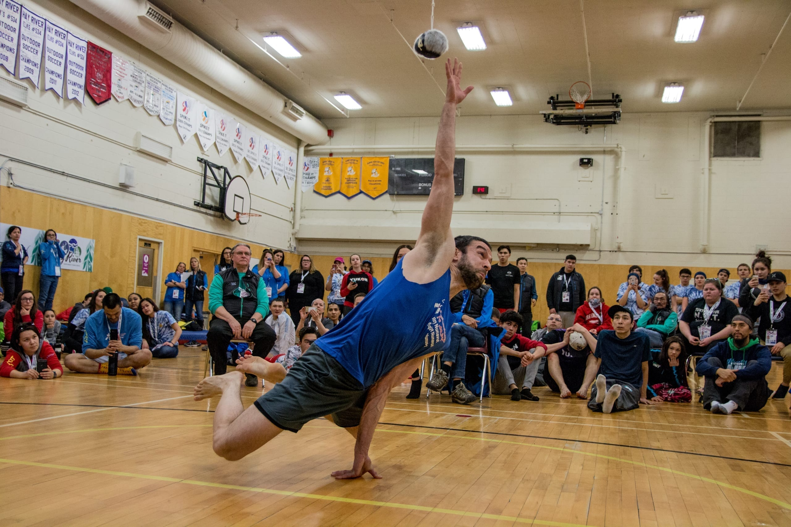 Arviat's Drew Bell reaches out to graze the sealskin ball during a record setting attempt in the one-hand reach at the 2018 Arctic Winter Games in Fort Smith, NWT. Bell's reach of 5 ft. 7 in. surpassed the previous record by one inch. NNSL file photo