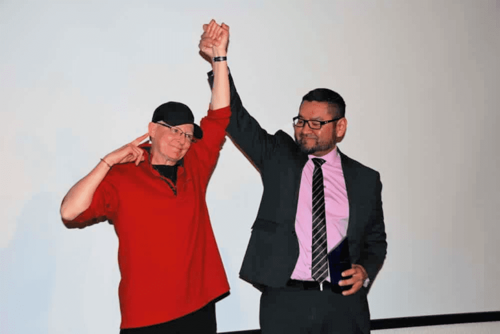 Robin Mercer-Sproule, left, raises her hand raised triumphantly with Alfred Moses, then-minister of Municipal and Community Affairs, after she was inducted into the athletes category of the NWT Sport Hall of Fame at the Explorer Hotel on Nov. 23, 2018. NNSL file photo