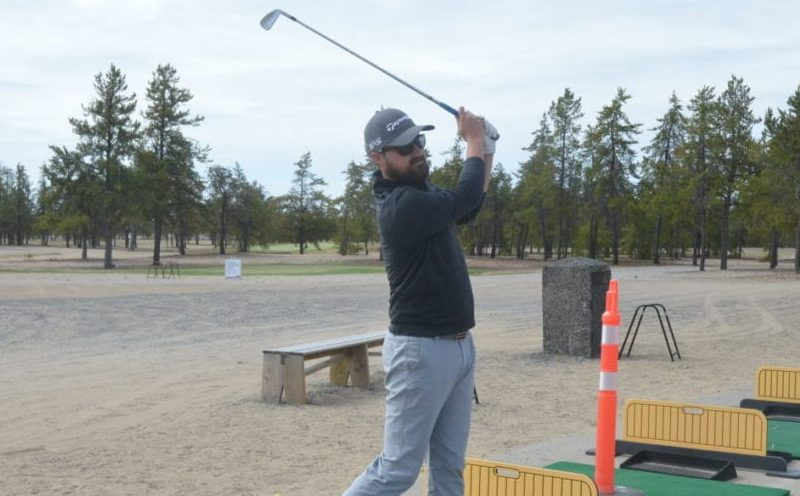 Cole Marshall, general manager and head pro at the Yellowknife Golf Club, admires a practice shot on the driving range on Sunday. Note the orange pylon to Marshall's left, indicating that every other tee box on the range is closed off due to distancing procedures instituted at the club this season. James McCarthy/NNSL photo