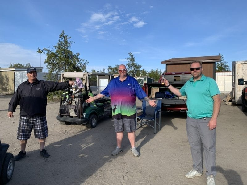 Daryl Snow, left, and Chris Hewitt, right, accept their physically-distanced trophies from Shaun Morris, president of the Mediocre Golf Association's Yellowknife chapter, after winning the team portion of the Rebel Beach Am-Am at the Yellowknife Golf Club on Saturday. photo courtesy of Shaun Morris