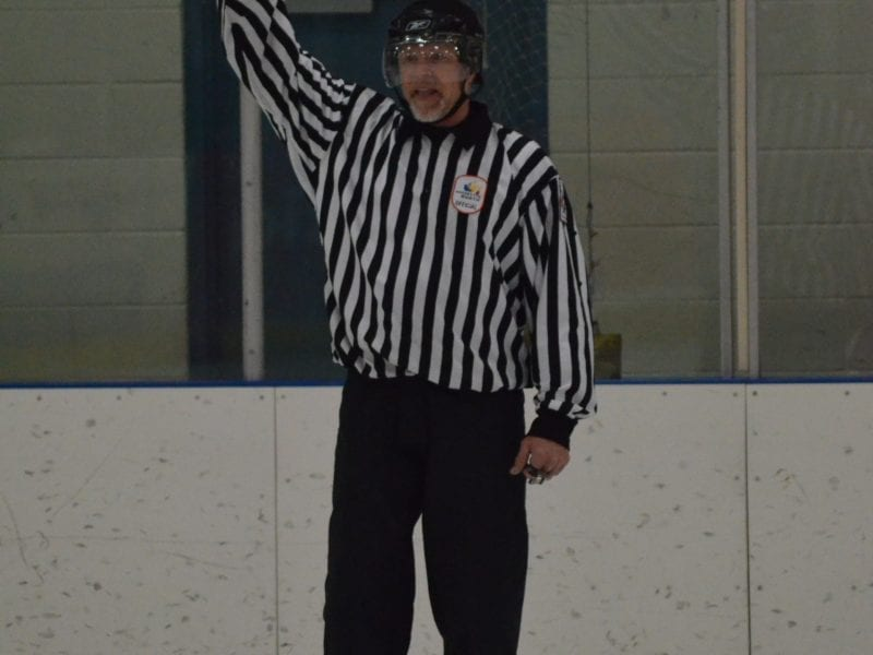 Craig Hockridge signals to the visitors bench about line changes during a game at the Multiplex in 2014. Hockridge, a long-time hockey official in the North and referee-in-chief for Hockey North, died on June 17 after succumbing to a massive stroke. NNSL file photo
