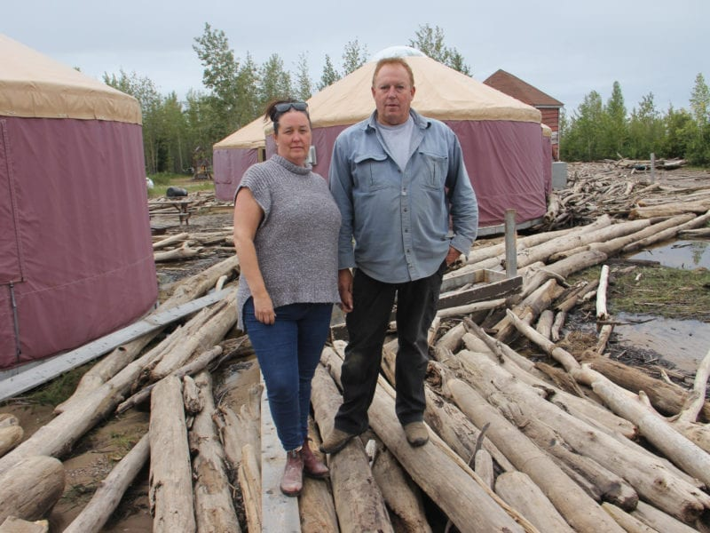 Kathy McBryan, left, and Fraser Pike — the owner/operators of the 2 Seasons Adventures campground on the shore of Great Slave Lake — stand in front of yurts moved and damaged by high water, wind and driftwood on the evening of Aug. 29. Paul Bickford/NNSL photo