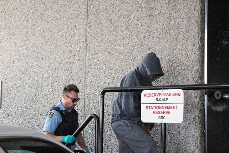 Brendan Burke/NNSL photo Wilfred Abraham, 54, covers his face as he enters a Yellowknife courthouse in handcuffs Thursday. Abraham has been charged with second-degree murder for the death of 48-year-old Ralph Sifton.