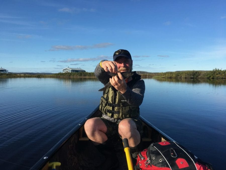 John MacEachern holds an Arctic Grayling he caught in Point Lake by Peterson's Point Lake Lodge. photo courtesy of Peterson's Point Lake Lodge