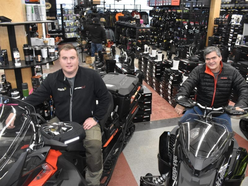 Polar Tech owner Joey Sutton, left, and Mike Bryant, project manager, sit on some of the remaining snow machines after half of the 200 the company ordered for 2020 have already been sold. Blair McBride/NNSL photo