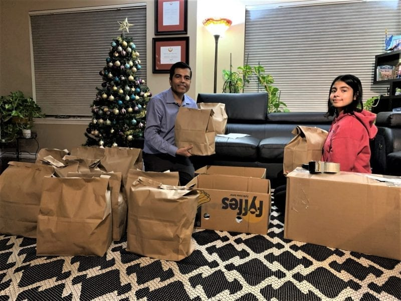 Sudhir Jha, left, and his daughter Isha prepare food packages before shipping them to families in Cambridge Bay, Nunavut. photo courtesy of Sudhir Jha