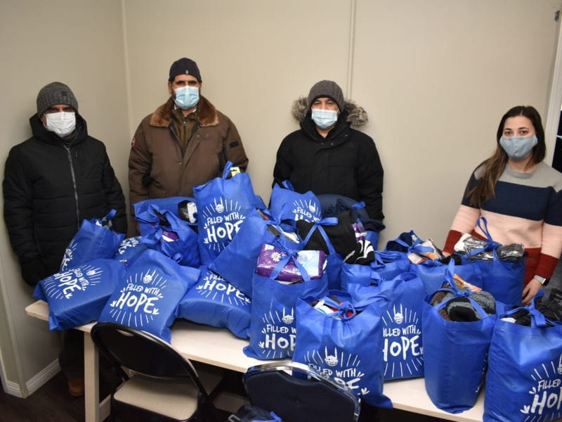 Zaka-Ullah, left, Nazim Awan, chair of the Islamic Centre of Yellowknife (ICYK), Asif Mirza and Kimberly Gagnon, program coordinator for street outreach at the Yellowknife Women's Society organize the 50 winter warmth kits the ICYK donated to the Women's Society, on Wednesday. Blair McBride/NNSL photo