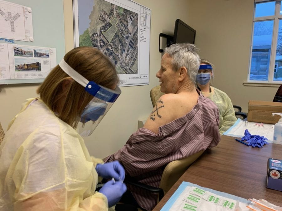 A health care worker, left, prepares to administer the Moderna vaccine to Bruce Jonasson at AVENS Manor in Yellowknife, on Thursday. GNWT image