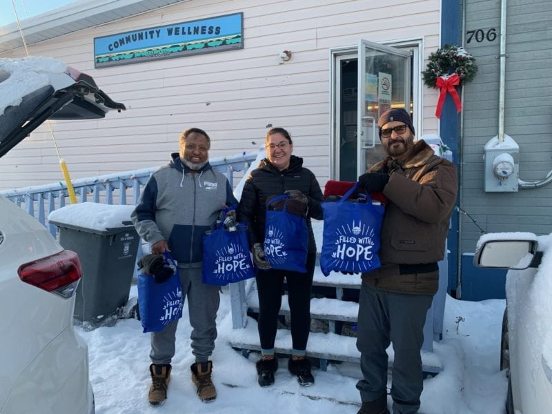 Abdi-Kareem Yalahow, left, a member of the executive committee of the Islamic Centre of Yellowknife (ICYK) gives winter warmth and hygienic kits to Jennifer Drygeese, director of community wellness with the Yellowknives Dene First Nation, along with Nazim Awan, chair of the ICYK, on Monday. photo courtesy of YKDFN