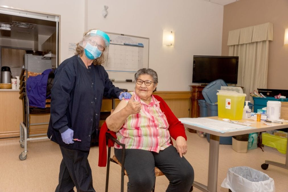 A health care worker with the Northwest Territories Health and Social Services Authority, left, prepares to give the Covid-19 vaccine to Caroline Douglas at the Jimmy Erasmus Seniors Home in Behchoko. GNWT image
