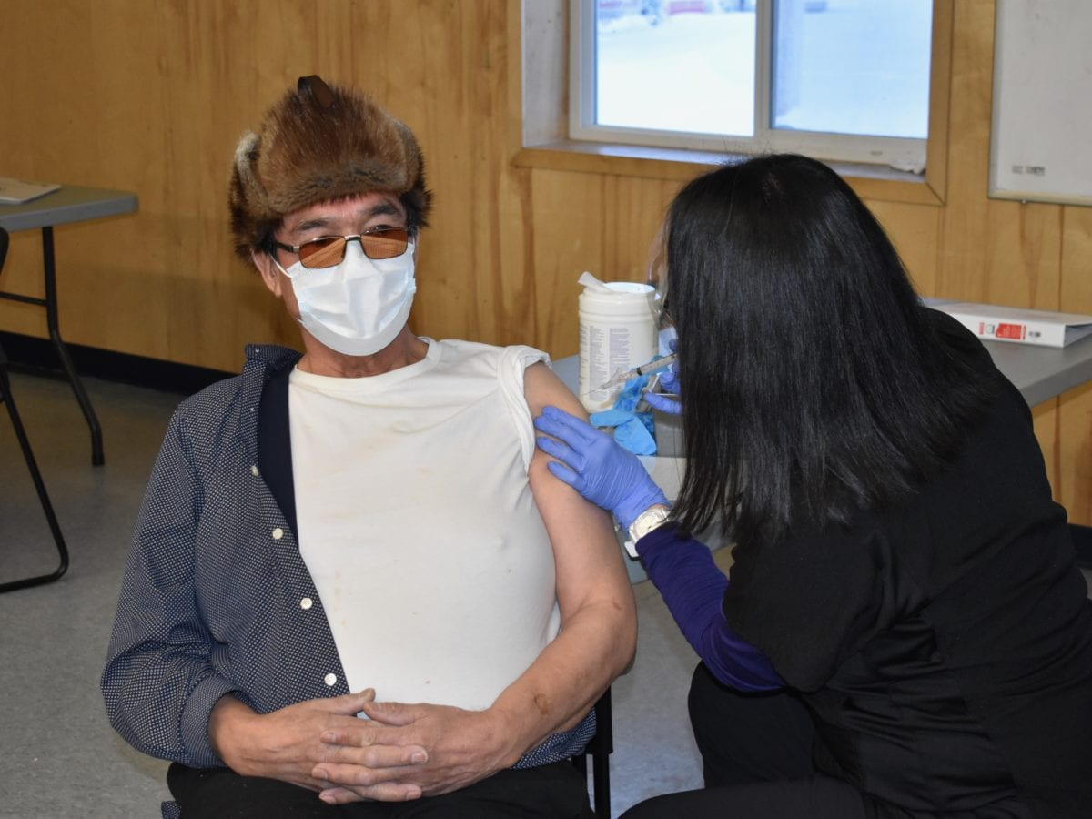 Wekweeti chief Charlie Football, left, receives his Covid-19 vaccination from nurse Lianne Mantla, in the Youth Centre, on Wednesday. Blair McBride/NNSL photo