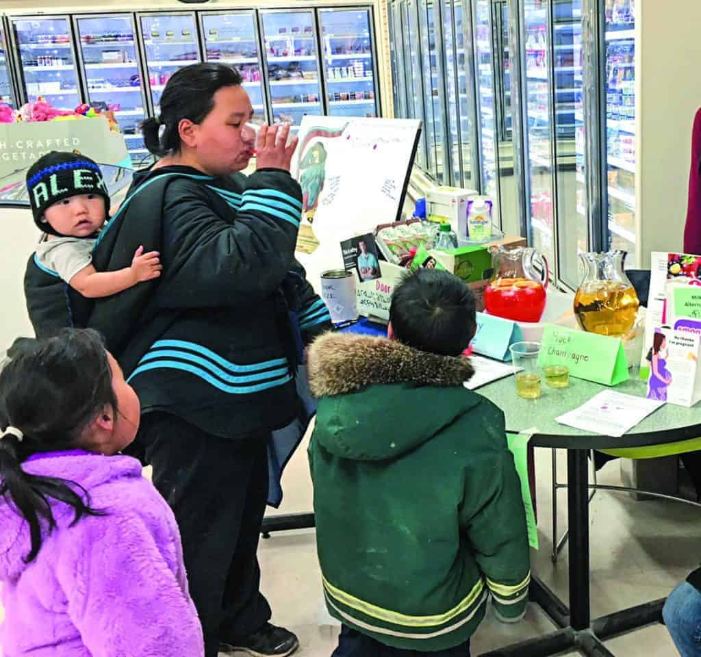 Tiriaq Aaruaq tried out a delicious Shirley Temple mocktail while children Alex, Jessie, and Isaac looked on during a Baker Lake Prenatal Nutrition Project event to celebrate International FASD day in September of 2018. photo courtesy Laurel Kreuger