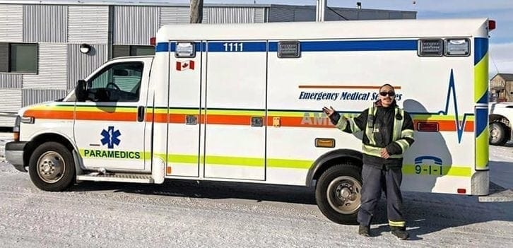 Robert Alice Pootoogo stands alongside an ambulance that Gjoa Haven received via sealift in September, the first ambulance in the community's history, according to Mayor Joanni Sallerina. Tamara Tarasoff photo.