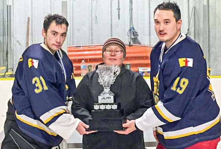 Frances Uppahuak, on behalf of Calm Air, presents the 2018 JLM Calm Air Cup senior men's championship trophy to Rankin Inlet's James Merritt, left, and Wendel Kaludjak in Arviat on Jan. 28, 2018. NNSL file photo
